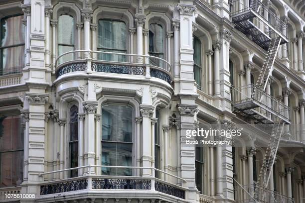bay window of typical cast iron building with fire escapes in chelsea, new york city - ニューヨーク ソーホー ストックフォトと画像