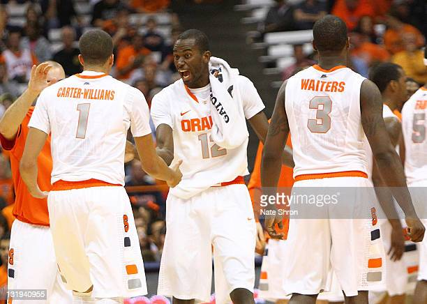 Baye Keita of the Syracuse Orange celebrates with teammates Michael CarterWilliams and Dion Waiters during the game against the College of Saint Rose...