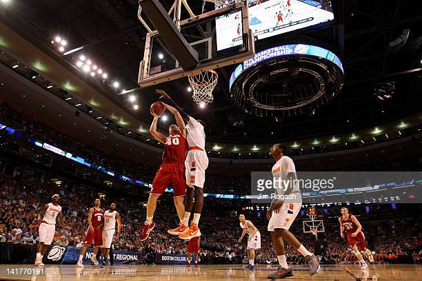 Baye Keita of the Syracuse Orange contests the shot of Jared Berggren of the Wisconsin Badgers during their 2012 NCAA Men's Basketball East Regional...