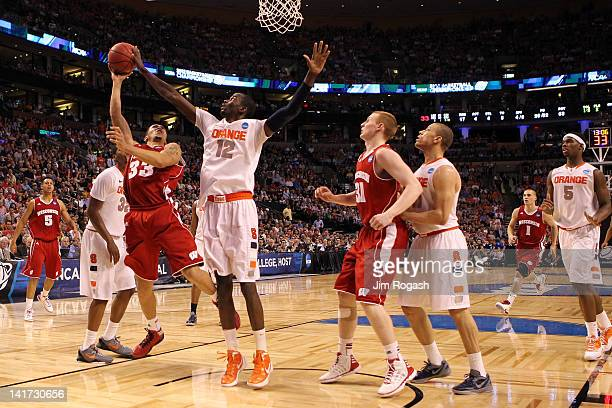 Baye Keita of the Syracuse Orange fouls Rob Wilson of the Wisconsin Badgers thduring their 2012 NCAA Men's Basketball East Regional Semifinal game at...