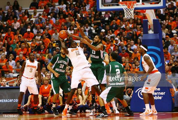 Baye Keita of the Syracuse Orange reaches as he holds on to the ball against Antonio Green of the Eastern Michigan Eagles during the game at the...