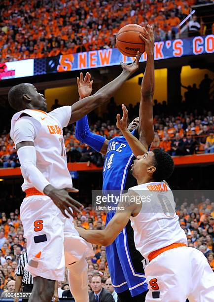 Baye Moussa Keita and and Michael Gbinije of the Syracuse Orange and Rasheed Sulaimon of the Duke Blue Devils react to a loose ball during the first...