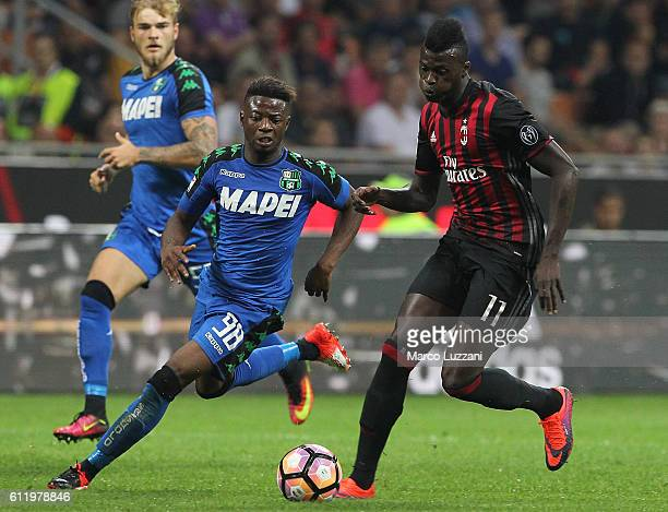 Baye Niang of AC Milan is challenged by Claude Adjapong of US Sassuolo during the Serie A match between AC Milan and US Sassuolo at Stadio Giuseppe...