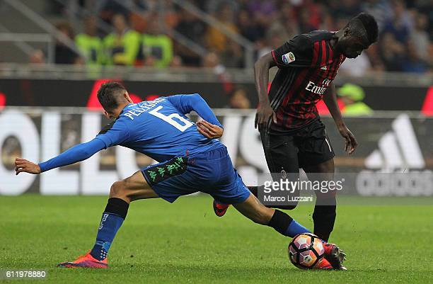 Baye Niang of AC Milan is challenged by Lorenzo Pellegrini of US Sassuolo during the Serie A match between AC Milan and US Sassuolo at Stadio...