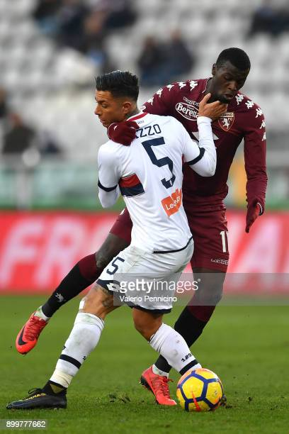 Baye Niang of Torino FC is challenged by Armando Izzo of Genoa CFC during the serie A match between Torino FC and Genoa CFC at Stadio Olimpico di...