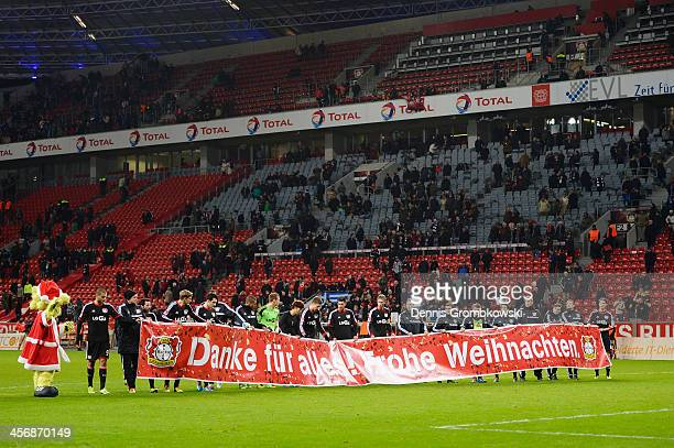 Bayer Leverkusen players present a banner wishing a Merry Christmas to their fans after the Bundesliga match between Bayer Leverkusen and Eintracht...