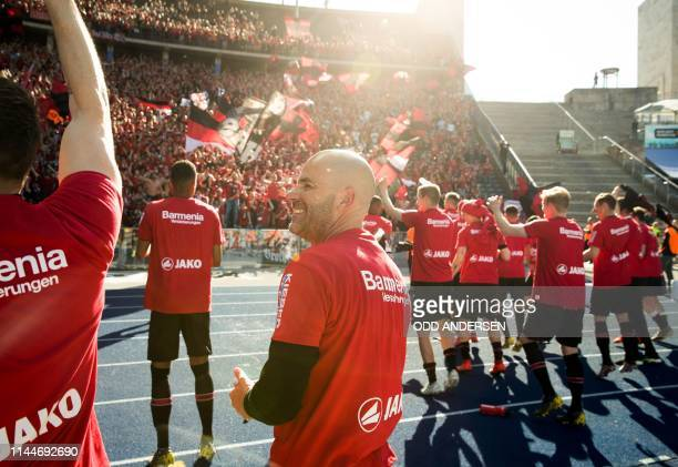 Bayer Leverkusen's Dutch head coach Peter Bosz and players celebrate with their fans after the German first division Bundesliga football match Hertha...