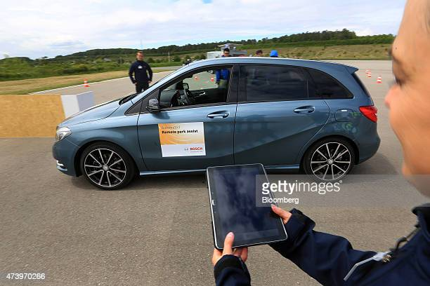 A Bayerische Motoren Werke AG automobile is parked via a mobile device remote control during a parking assist app demonstration at the Robert Bosch...