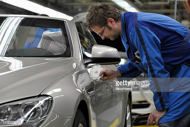A Bayerische Motoren Werke AG employee performs the final checks on a BMW 6 Series cabriolet automobile at the company's factory in Dingolfing...