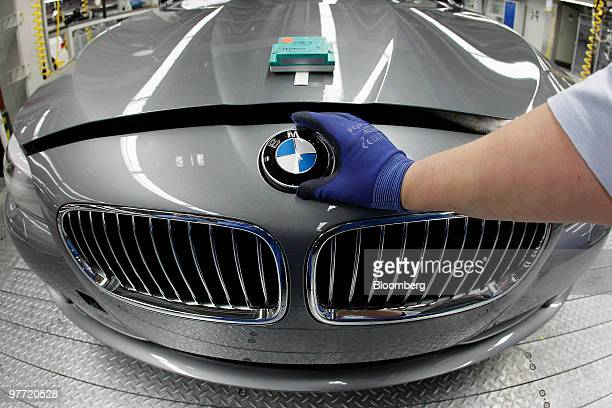 A Bayerische Motoren Werke AG employee puts the hood ornament logo on a 5series automobile at the company's factory in Dingolfing Germany on Monday...