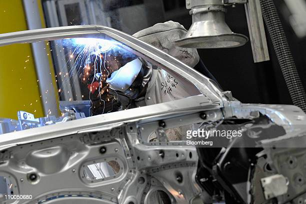A Bayerische Motoren Werke AG employee welds body parts on a BMW 6 Series cabriolet automobile at the company's factory in Dingolfing Germany on...