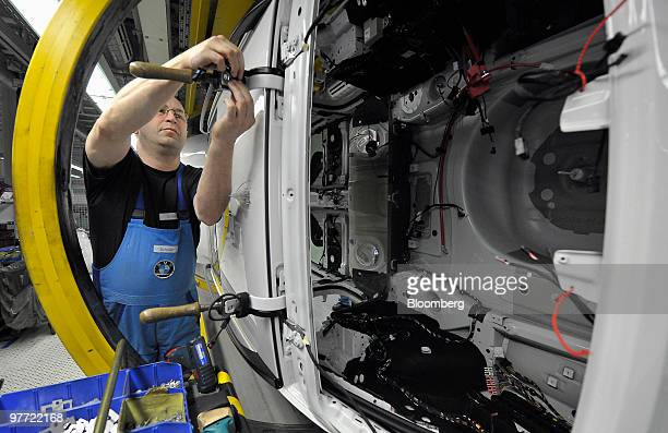 A Bayerische Motoren Werke AG employee works on the GTseries automobile assembly line at the company's factory in Dingolfing Germany on Monday March...