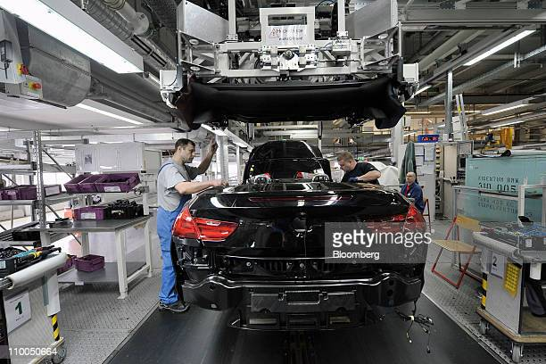 Bayerische Motoren Werke AG employees install the folding roof to a BMW 6 Series cabriolet automobile at the company's factory in Dingolfing Germany...