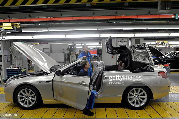 Bayerische Motoren Werke AG employees perform the final examination on a BMW 6 Series cabriolet automobile at the company's factory in Dingolfing...
