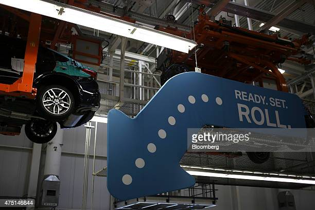 Bayerische Motoren Werke AG vehicles descend from the ceiling after having their wheels installed at the BMW Manufacturing Co assembly plant in Greer...