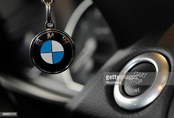A Bayerische Motoren Werke logo is seen on a key ring next to a car's ignition start button at a dealership in Rosenheim Germany on Tuesday May 18...