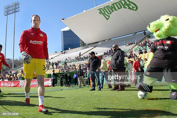 Bayern 04 Leverkusen goalie Niklas Lomb walks off the field as the mascot looks on before the Florida Cup between Estudiantes and Bayer 04 Leverkusen...