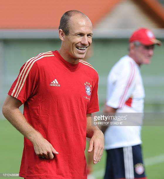 Bayern Dutch midfielder Arjen Robben laughs as on can be seen Bayern Munich's head coach Jupp Heynckes during a training session in Munich southern...