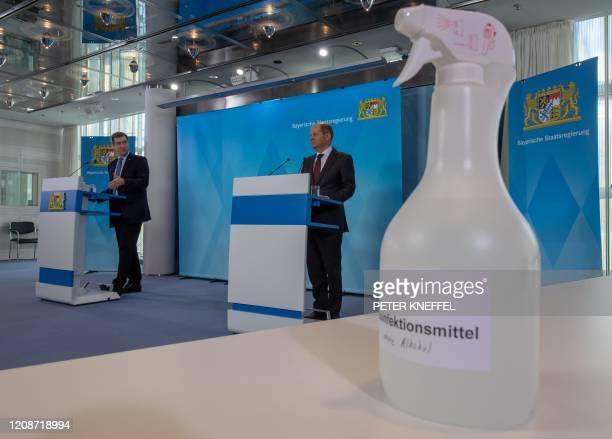 Infektionsmittel steht auf einem Tisch während Markus Söder Ministerpräsident von Bayern und Olaf Scholz Bundesminister der Finanzen eine...