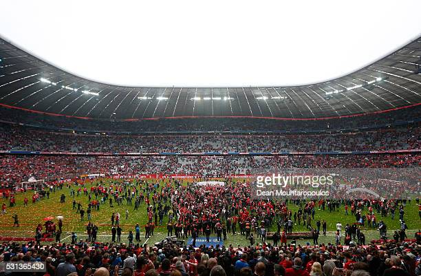 Bayern Muenchen fans celebrate on the pitch after the Bundesliga match between FC Bayern Muenchen and Hannover 96 at Allianz Arena on May 14 2016 in...