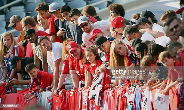 Bayern Muenchen fans wait for players signing autographs after a training session ahead of the team's friendly match against AC Milan on Wednesday at...