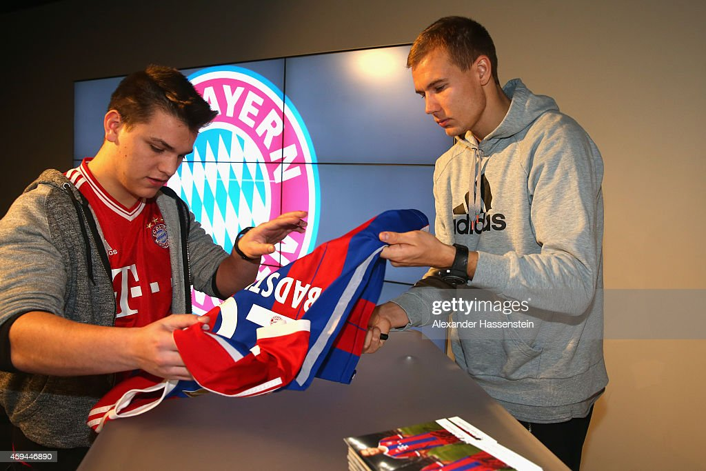 FC Bayern Muenchen player Holger Badstuber signs autographs during his visit at the FC Bayern Erlebniswelt museum at Allianz Arena on November 23, 2014 in Munich, Germany.