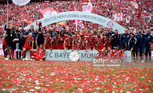 Bayern Muenchen players and staff pose with the Championship trophy in celebration of the 67th German Championship title following the Bundesliga...