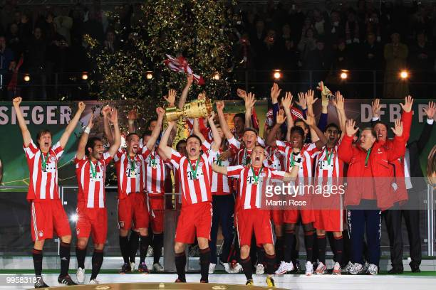 Bayern Muenchen players celebrate with the DFB Cup trophy following their victory at the end of the DFB Cup final match between SV Werder Bremen and...