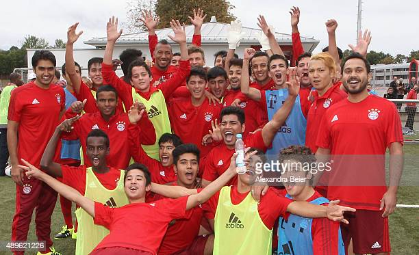 Bayern Muenchen players Jerome Boateng, Thomas Mueller and Thiago pose for the media together with refugee youths during a training session at...
