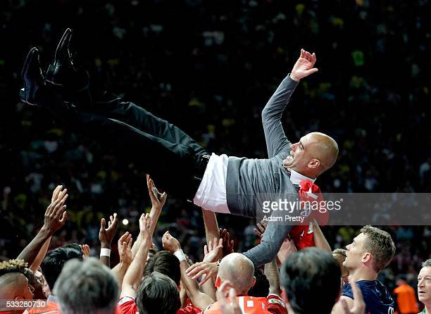 Bayern Muenchen players lift head coach Josep Guardiola after winning the DFB Cup Final between Bayern Muenchen and Borussia Dortmund at...