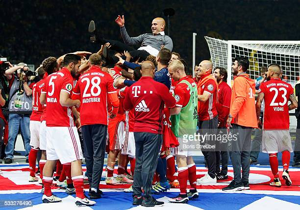 Bayern Muenchen players lift their head coach Pep Guardiola after winning the DFB Cup Final in a penalty shootout against Borussia Dortmund at...