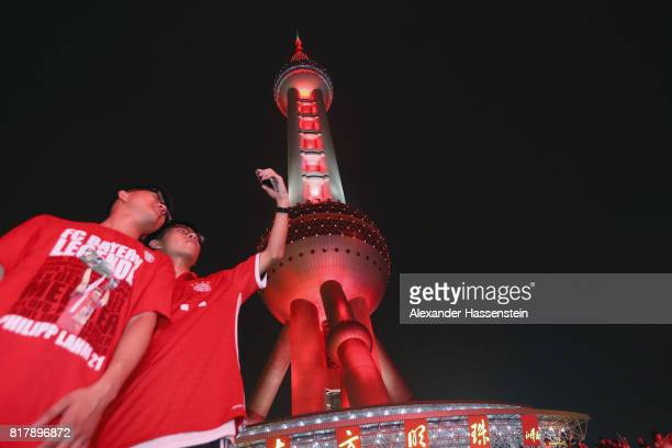Bayern Muenchen supportes take selfies as the Shanghai Oriental Pearl Tower e is illuminated in FC Bayern Muenchen colors during the Audi Summer Tour...