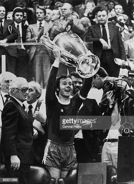Bayern Munich captain Franz Beckenbauer holds his trophy aloft after his team beat Leeds United 20 in the European Cup final at Parc des Princes...