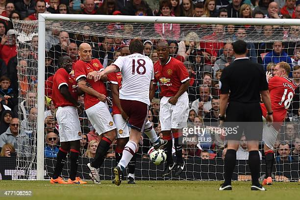 Bayern Munich legend Michael Tarnat hits a free kick that flies straight under the defensive wall of Manchester Utd legends Dwight Yorke Jaap Stam...