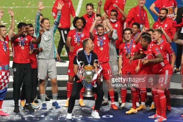Bayern Munich players and Bayern Munich's German coach Hans-Dieter Flick celebrate with the trophy after the UEFA Champions League final football...