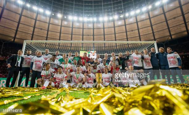 Bayern Munich players celebrate with the DFB Pokal following their sides victory in the DFB Cup final between RB Leipzig and Bayern Muenchen at...
