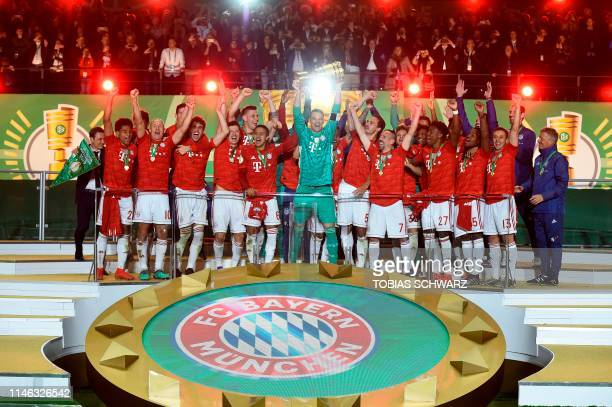 Bayern Munich players celebrate with the trophy after the German Cup Final football match RB Leipzig v FC Bayern Munich at the Olympic Stadium in...