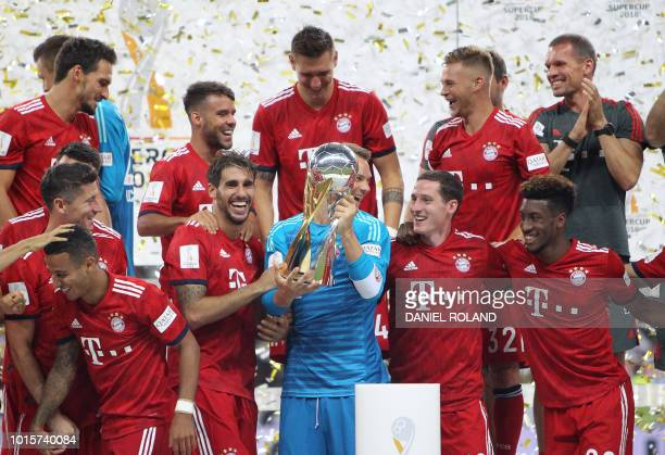 Bayern Munich players celebrate with the trophy after winning the German Supercup football match between Eintracht Frankfurt and Bayern Munich in...