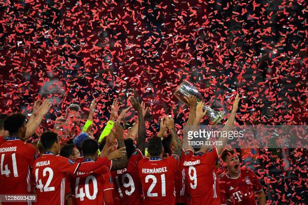 Bayern Munich players celebrate with the trophy after winning the UEFA Super Cup football match between FC Bayern Munich and Sevilla FC at the Puskas...