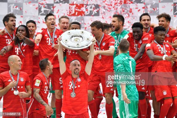TOPSHOT Bayern Munich players including Bayern Munich's French midfielder Franck Ribery celebrate with the trophy after the German First division...