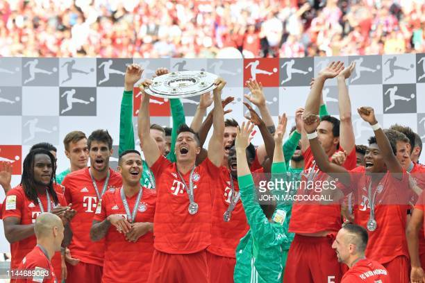 Bayern Munich players including Bayern Munich's Polish forward Robert Lewandowski celebrate with the trophy after the German First division...