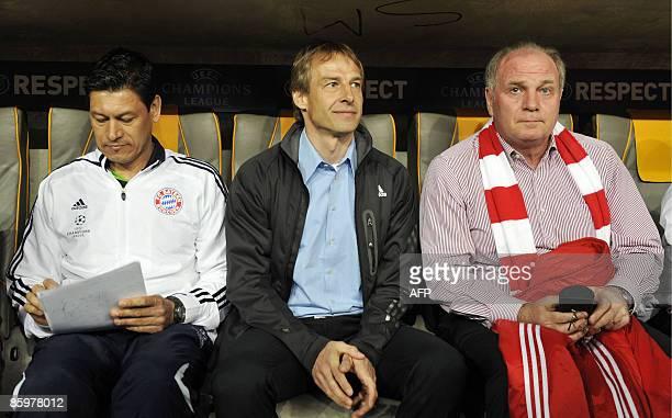 Bayern Munich's assistent coach Martin Vasquez coach Juergen Klinsmann and team manager Uli Hoeness sit on the bench before the second leg Champions...