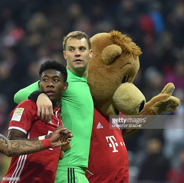 Bayern Munich's Austrian defender David Alaba and Bayern Munich's goalkeeper Manuel Neuer react with the Bayern Munich mascot after the German first...