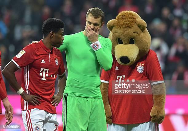 Bayern Munich's Austrian defender David Alaba and Bayern Munich's goalkeeper Manuel Neuer speak together beside the Bayern Munich mascot after the...