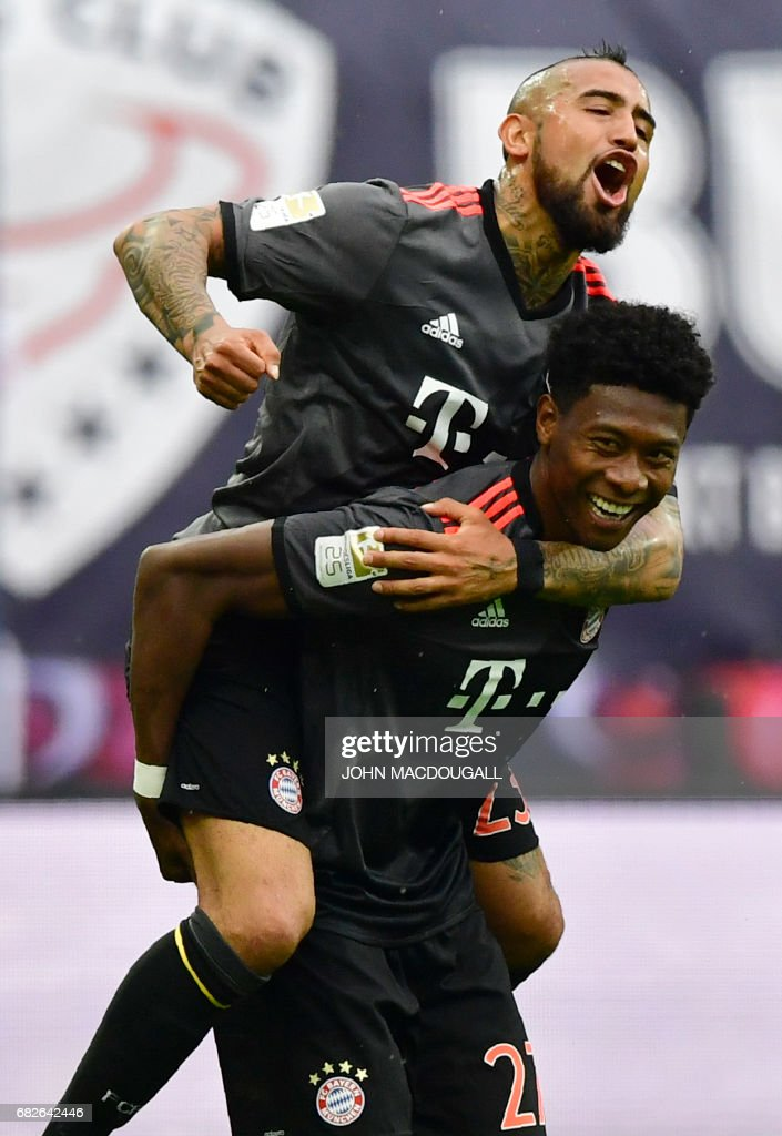 Bayern Munich's Austrian defender David Alaba (bottom) and Bayern Munich's Chilean midfielder Arturo Vidal celebrate after Alaba scored the 4-4 equalizer during the German first division Bundesliga football match between RB Leipzig and FC Bayern Munich on May 13, 2017 in Leipzig, eastern Germany. / AFP PHOTO / John