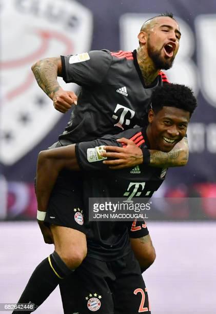 Bayern Munich's Austrian defender David Alaba and Bayern Munich's Chilean midfielder Arturo Vidal celebrate after Alaba scored the 4-4 equalizer...