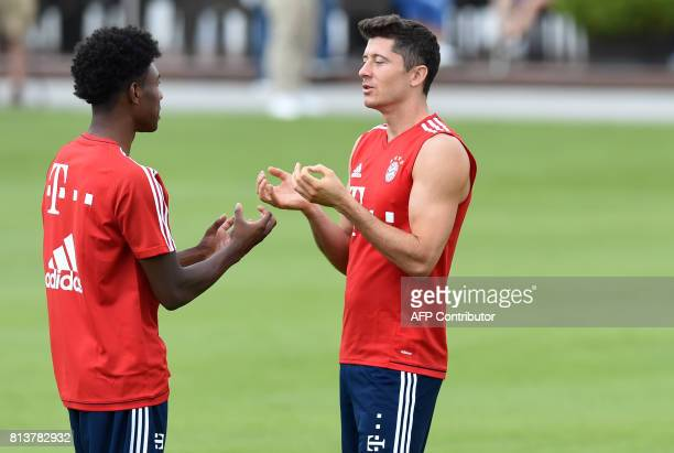 Bayern Munich's Austrian defender David Alaba and Bayern Munich's Polish forward Robert Lewandowski gesture as they attend a training session of...