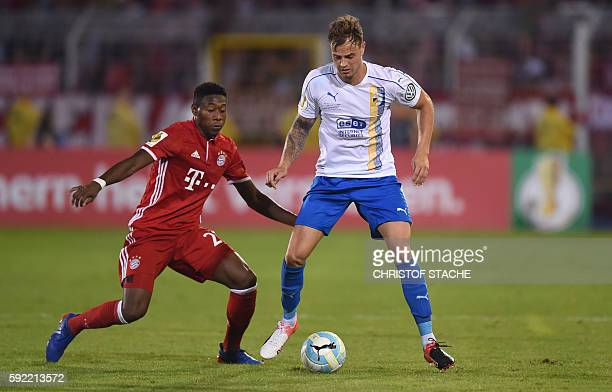 Bayern Munich's Austrian defender David Alaba and Jena's striker Timmy Thiele vie for the ball during the German Cup first round football match...