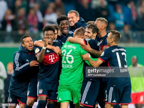 Bayern Munich's Austrian defender David Alaba celebrates with his teammates after winning the penalty shoot out and the match after the German Cup...