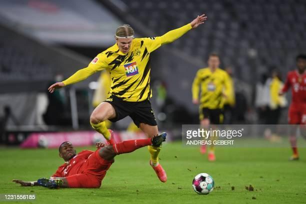 Bayern Munich's Austrian defender David Alaba fouls Dortmund's Norwegian forward Erling Braut Haaland during the German first division Bundesliga...